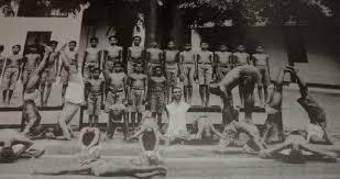 Krishnamacharya ensinando no Yogashala, Pattabhi Jois em Sirsana, no canto esquerdo.